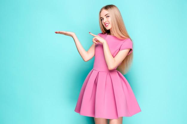 Улыбка красивая молодая женщина в розовом мини-платье позирует, представляя что-то Бесплатные Фотографии