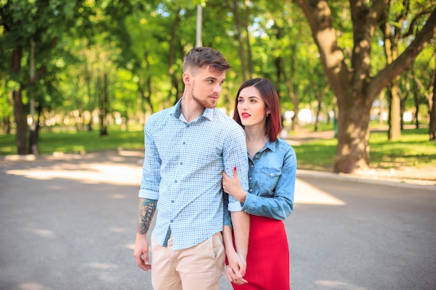 公園に立って、明るく晴れた日に笑って幸せな若いカップル 無料写真