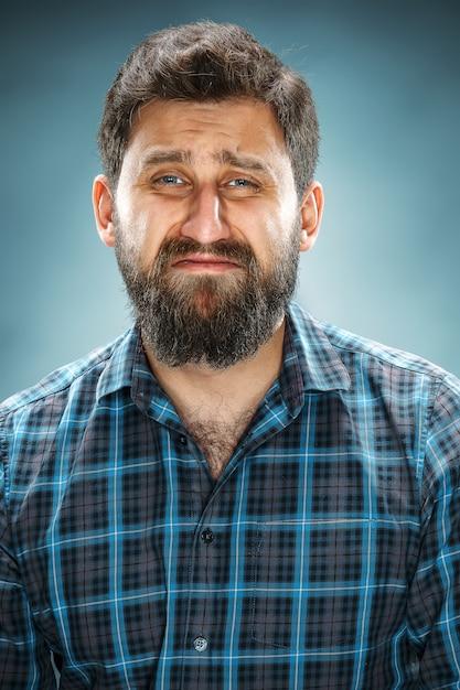 青いシャツを着て泣いている男 無料写真