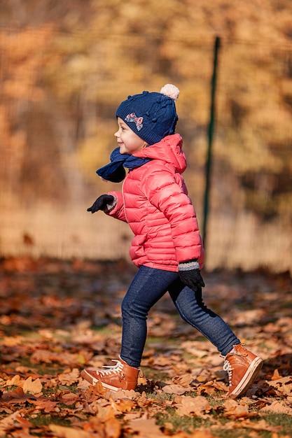 Маленькая девочка, играя в осенние листья Бесплатные Фотографии