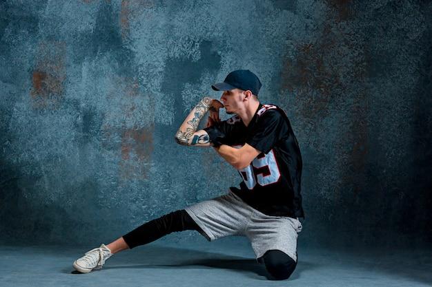 若い男は壁の背景にブレイクダンス。 無料写真