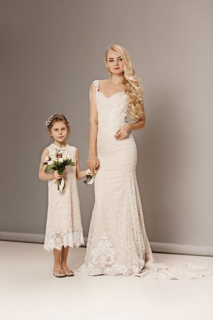 Маленькие красивые девушки с цветами, одетые в свадебные платья Бесплатные Фотографии