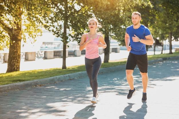 スポーティな女性と男の日の出の光の中で公園でジョギング 無料写真