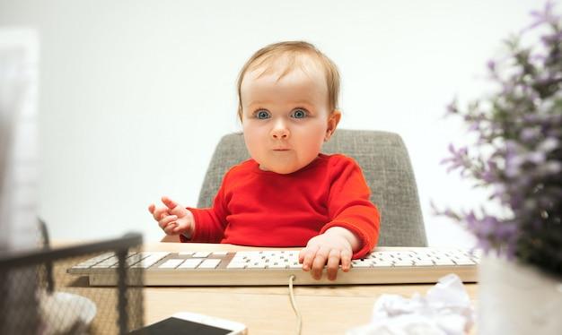 分離されたコンピューターのキーボードで座っている幸せな子供赤ちゃん女の子幼児 無料写真