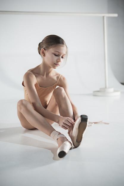 Красивая маленькая балерина надевает пуанты Бесплатные Фотографии