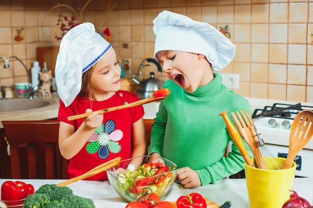 幸せな家族面白い子供たちはキッチンで新鮮な野菜サラダを準備しています 無料写真