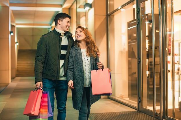 街で夜を楽しんでいる買い物袋と幸せなカップル 無料写真