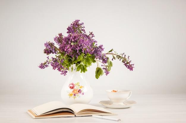 レモンとテーブルの上のライラックプリムローズの花束とお茶 無料写真