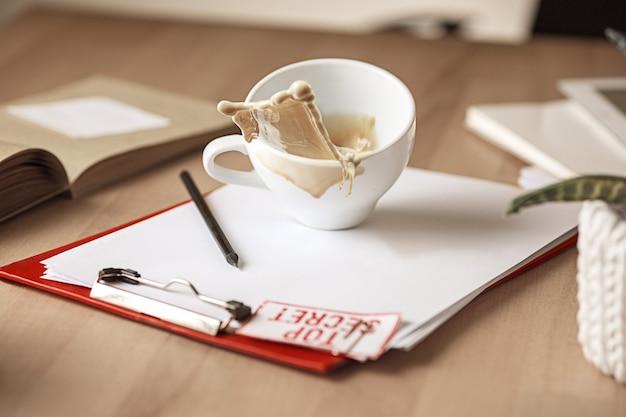 Кофе в белой чашке, разлив на стол утром на офисном столе Бесплатные Фотографии