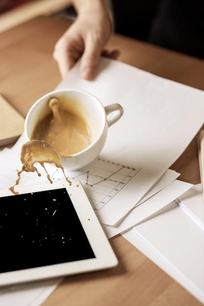 朝のオフィスのテーブルでテーブルの上にこぼれる白いカップのコーヒー 無料写真