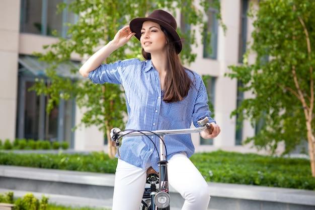 Красивая девушка в шляпе, езда на велосипеде на улице Бесплатные Фотографии