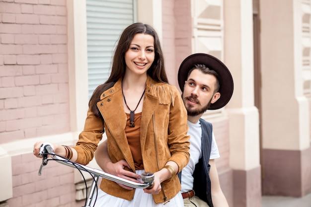 Молодая пара, стоя у стены и обниматься Бесплатные Фотографии