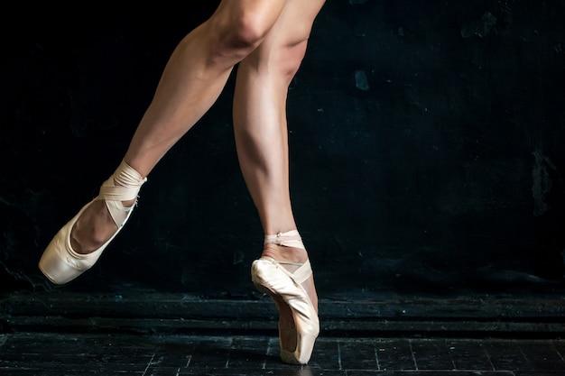 黒い木の床にクローズアップバレリーナの脚と拍 無料写真