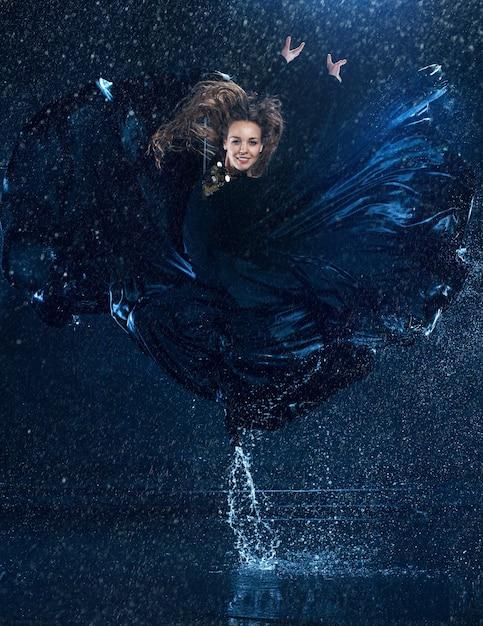 Молодая красивая современная танцовщица танцует под каплями воды Бесплатные Фотографии