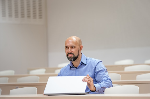 Молодой современный человек на университетской лекции работает на ноутбуке Premium Фотографии