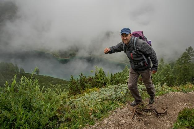 オーストリアアルプスのハイカーは、湖の周りの森の中の山道を歩く Premium写真