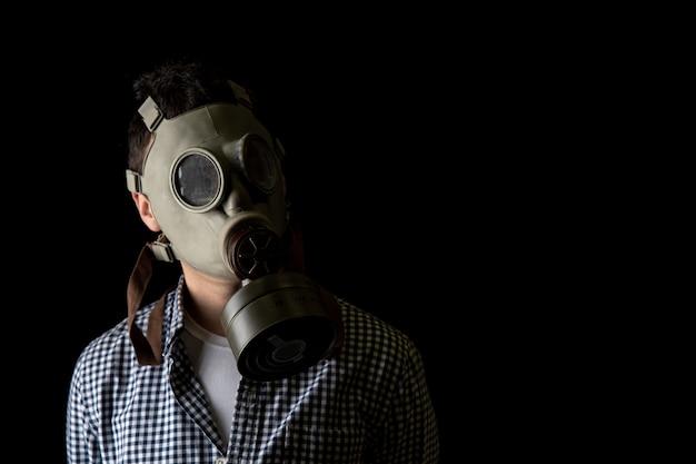 黒の背景に防毒マスクの男。コピースペース Premium写真