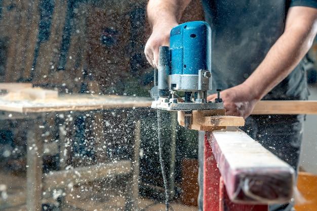 手動機械式カッターを使用して建具で木材を製粉します。おがくずが空を飛んでいます。コピースペース Premium写真