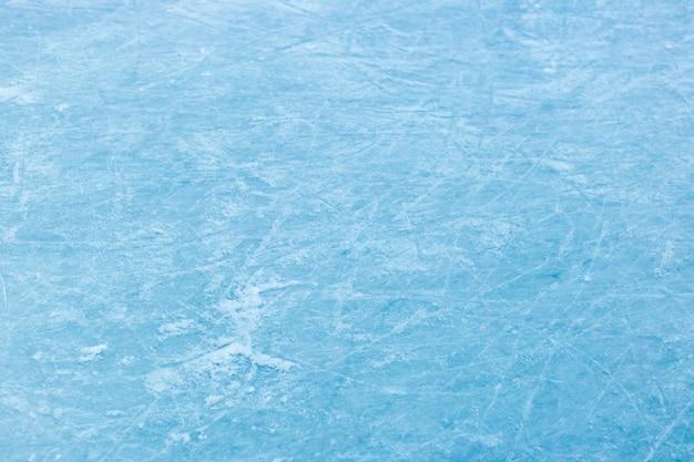 抽象的な氷のテクスチャ。自然の青い背景。氷の上でスケートのブレードの痕跡 Premium写真
