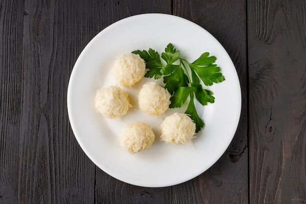 Сырные шарики в крабовой стружке - традиционная русская закуска к рождеству и новому году Premium Фотографии