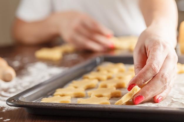 Руки делают рождественское печенье с металлическим резаком Premium Фотографии