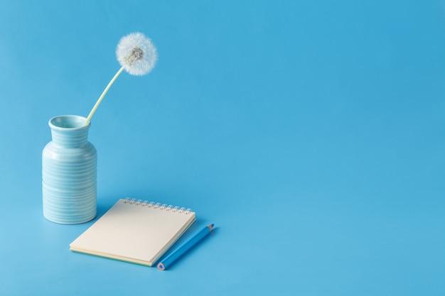 Блокнот, карандаш, одуванчик на синем фоне стола Premium Фотографии