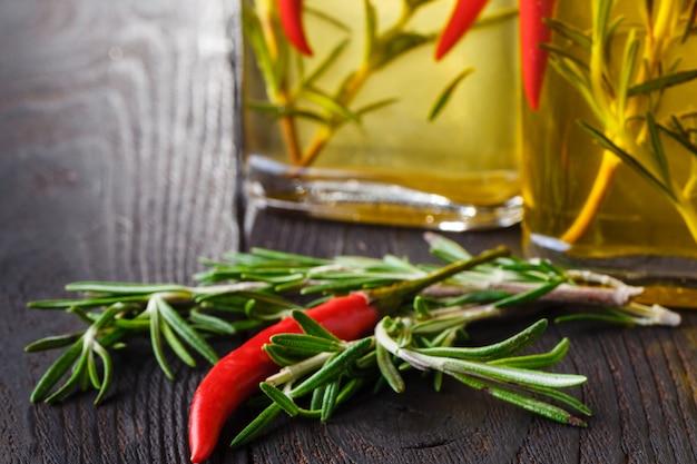Оливковое масло с различными специями на старый деревянный стол Premium Фотографии