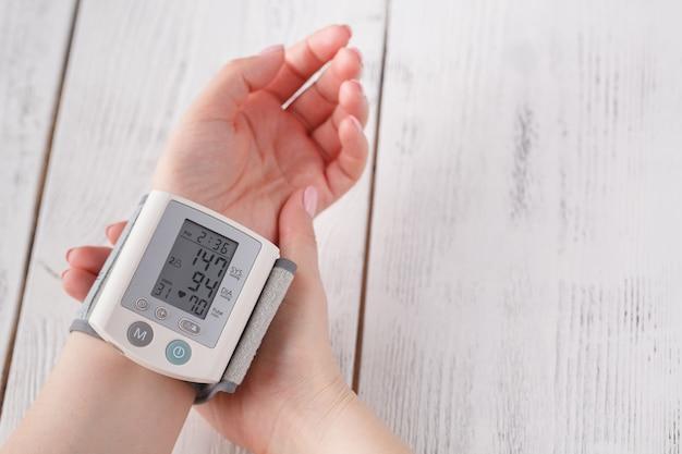 Женщина измеряет артериальное давление Premium Фотографии