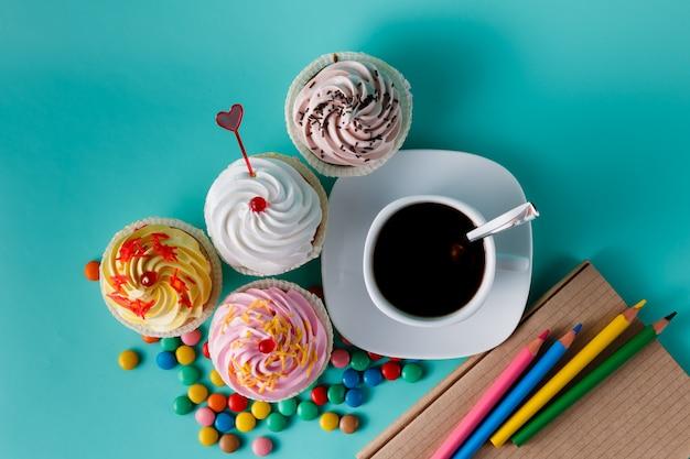 Кексы с красочными конфетти и чашкой кофе Premium Фотографии