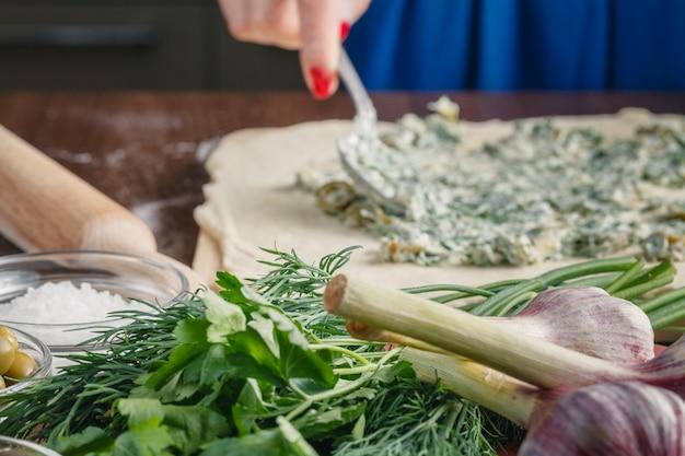 Приготовление хлеба чиабатта с чесноком, средиземноморскими оливками Premium Фотографии