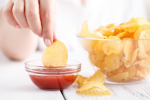 ケチャップとポテトチップス、女性はジャンクフードを食べる Premium写真