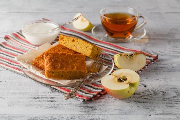 テーブルの上の木製のプレートにリンゴとティーカップを添えて甘いアップルケーキ Premium写真