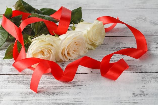 バラと木の板、バレンタインデーの背景、結婚式の日のリボン Premium写真