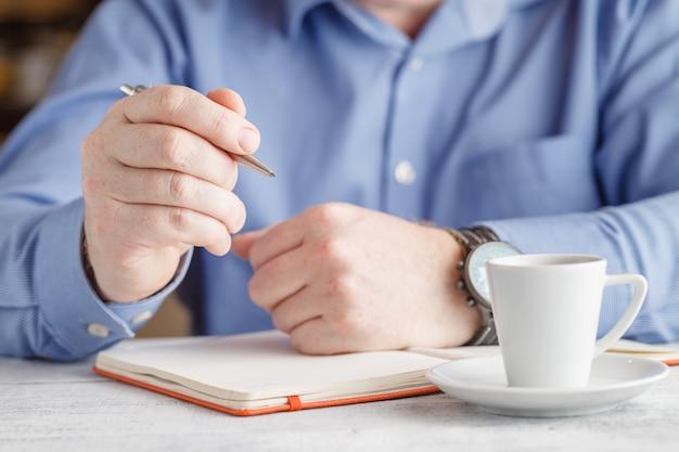 Изображение крупного плана человека выпивая вкусный кофе эспрессо на переднем плане Premium Фотографии