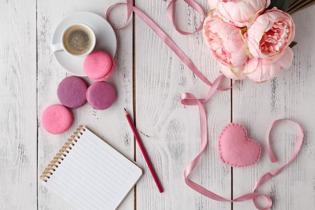 Кофе, торт макарон, чистая тетрадь, очки и цветок на розовом столе сверху. Premium Фотографии