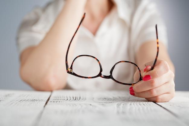 茶色のフレーム付きメガネを持っている女性の手 Premium写真