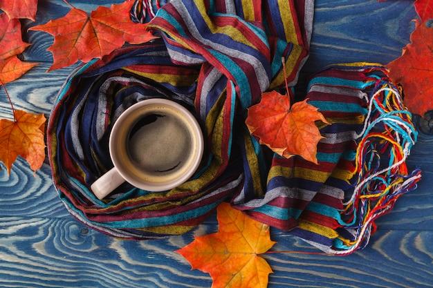 古い木製の表面にホットコーヒーカプチーノ、毛布、紅葉 Premium写真