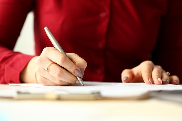 Женский офисный работник с серебряной ручкой, заполнив анкету Premium Фотографии