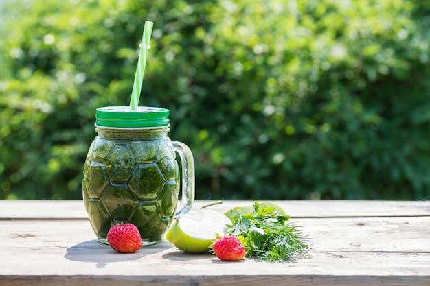 健康的な緑のスムージーと食材-パセリ、ディル、リンゴ、イチゴ。スーパーフード。コンセプトの健康食品。 Premium写真