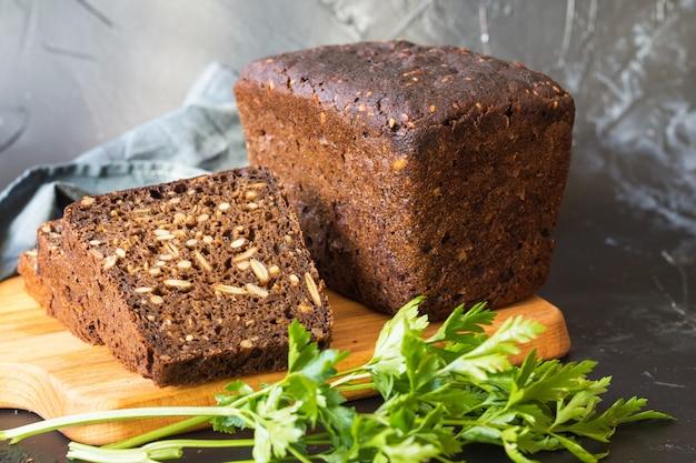 カボチャの種をまぶした小麦粉パン、まな板とパンのスライス Premium写真