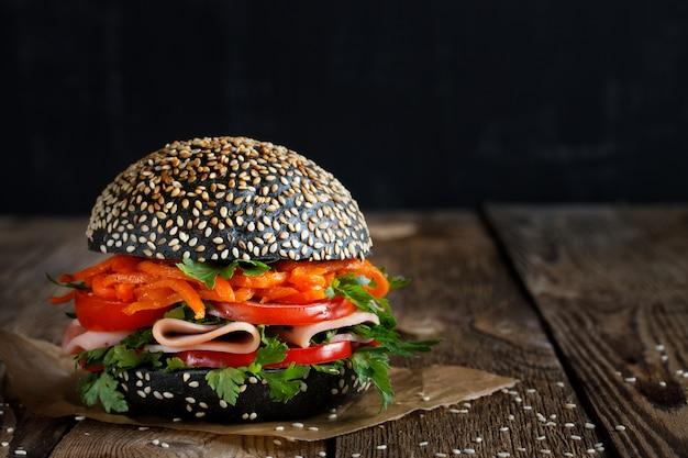 ゴマと新鮮な野菜(トマト、ピーマン)が入った新鮮な食欲をそそる明るいハンバーガー Premium写真