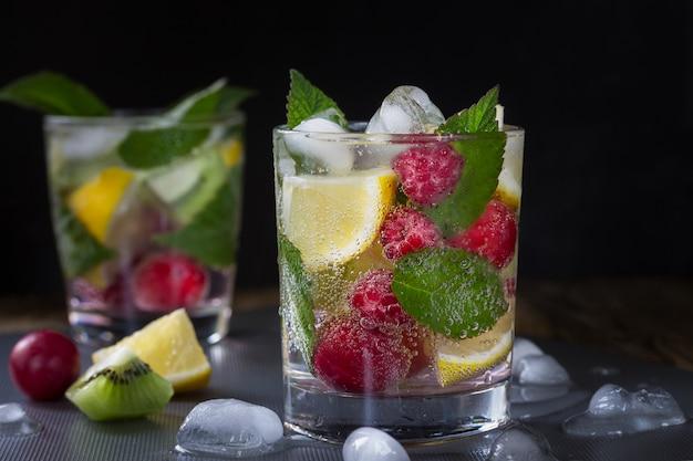Летний освежающий газированный напиток с ягодами и фруктами малина, лимон, киви и лед на темноте. макрос Premium Фотографии