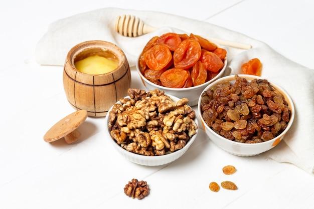 Набор сушеных ягод, фруктов и орехов, лежащих в тарелке (грецкие орехи, тыква, вишня, абрикос, яблоко, финики) Premium Фотографии