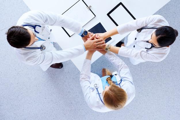 Профессиональные врачи рукопожатие в больнице. плоская планировка, вид сверху Premium Фотографии
