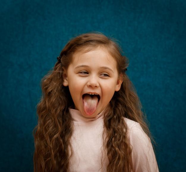 少女は舌を示しています Premium写真