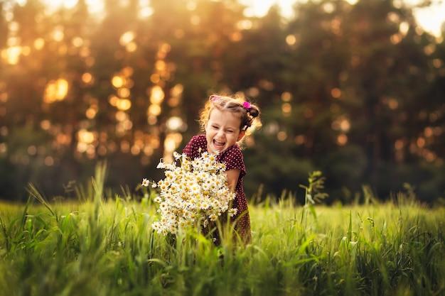 夏の自然の花を持つ少女 Premium写真