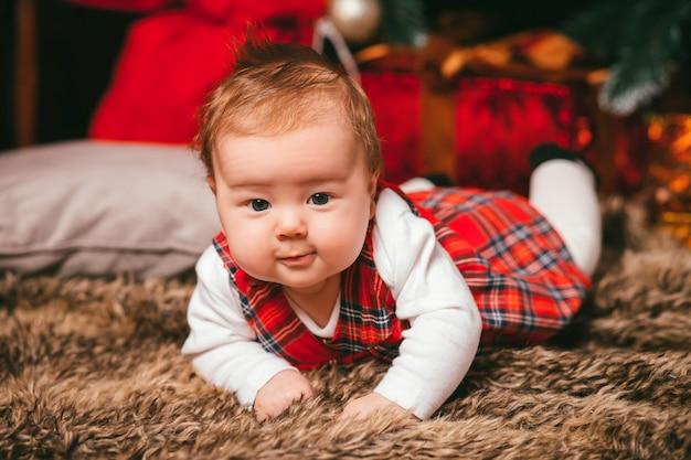 クリスマスツリーの横にある赤ちゃん Premium写真