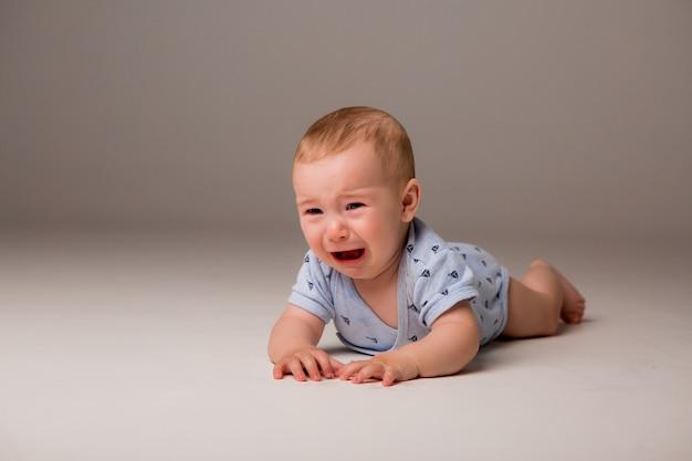 泣いている赤ちゃんは明るい背景に分離します。 Premium写真