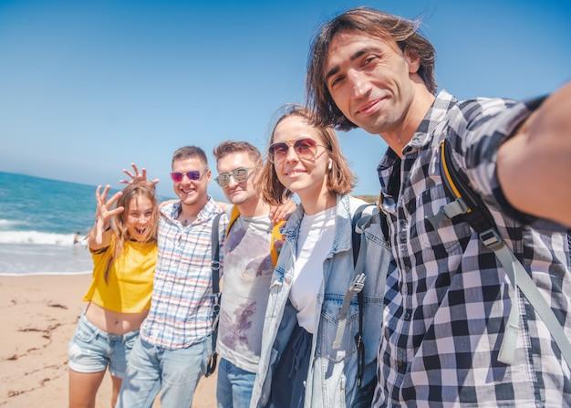 Компания группы счастливых объятий молодых симпатичных людей, студентов мужчин и женщин на солнечном пляже, концепция путешествия день дружбы путешествия отпуск Premium Фотографии