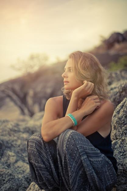 夕暮れ時の岩の上に座っている美しい若い女性 Premium写真